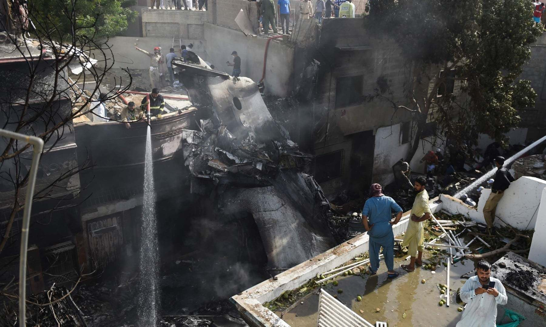 Firefighters spray water on the wreckage of a Pakistan International Airlines aircraft after it crashed at a residential area in Karachi on May 22. — AFP