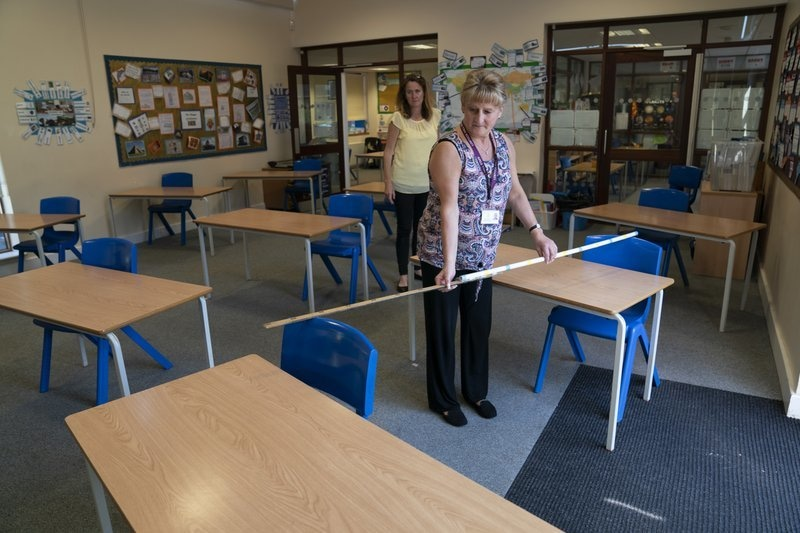 Year 6 teacher Jane Cooper uses a 2 metre length of ruler and pipe to check seat spacings in her classroom as measures are taken to prevent the transmission of coronavirus before the possible reopening of Lostock Hall Primary school in Poynton near Manchester, England, May 20. — AP