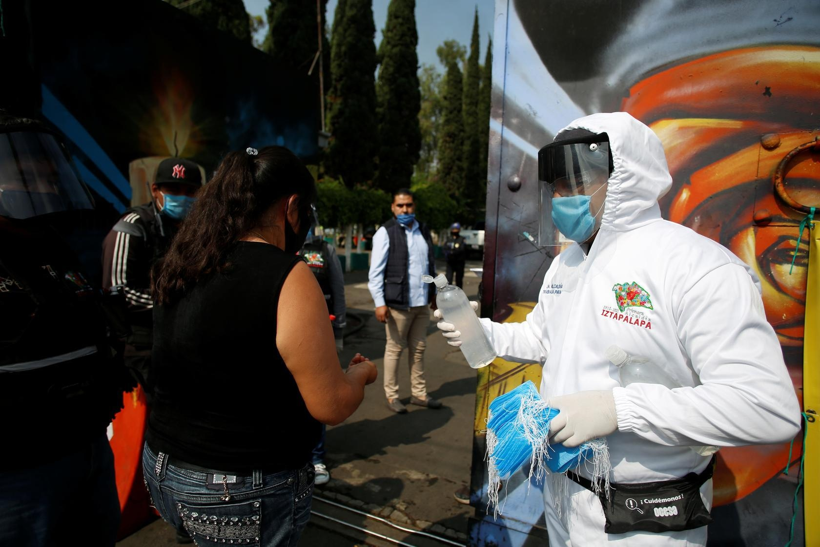 An employee of the municipality of Iztapalapa gives sanitising gel to a woman arriving to the San Nicolas Tolentino cemetery, amid Covid-19 outbreak in Mexico City, Mexico, May 9. — Reuters