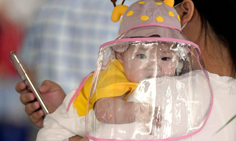 A baby with a face shield waits to board a plane at an airport in Wuhan, central China's Hubei Province, May 23. China on Saturday reported no new confirmed cases or deaths from the novel coronavirus. — AP
