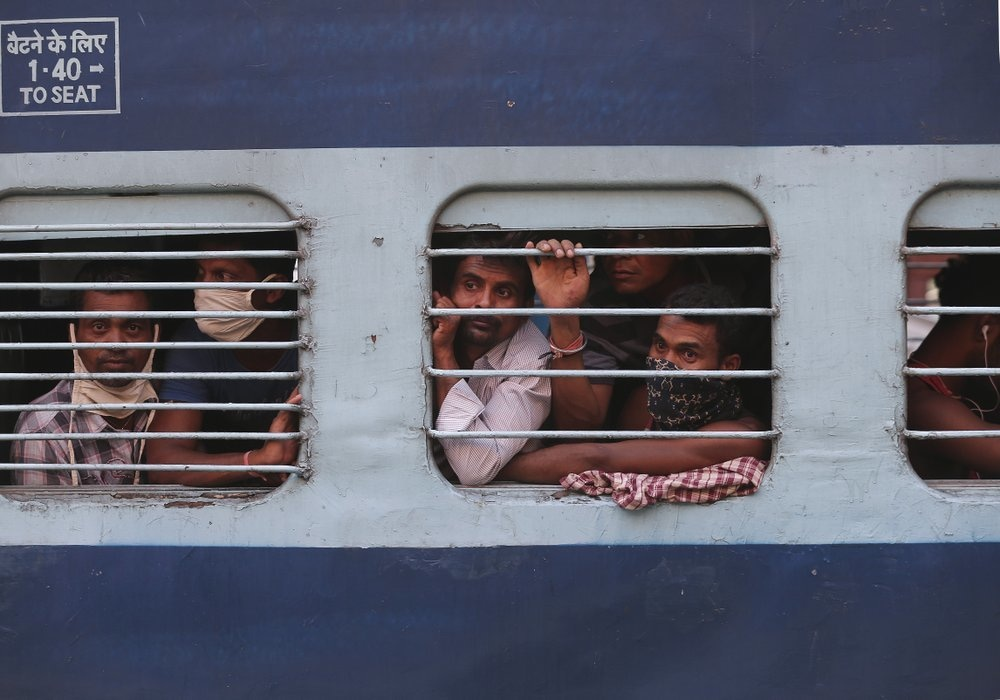 Migrant workers look out a train window before moving to their home states, at Hyderabad Railway Station in Hyderabad, India, May 23. — AP