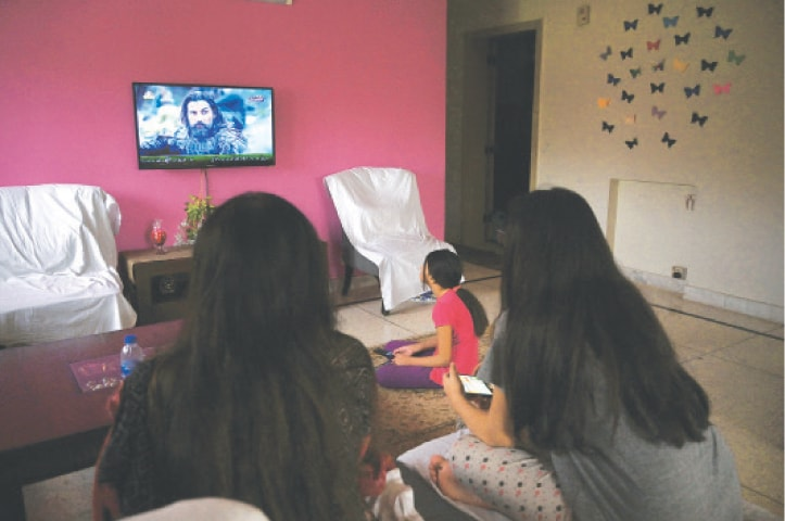 ISLAMABAD: A family watches a Turkish drama series telecast on state-run channel PTV Home.—AFP