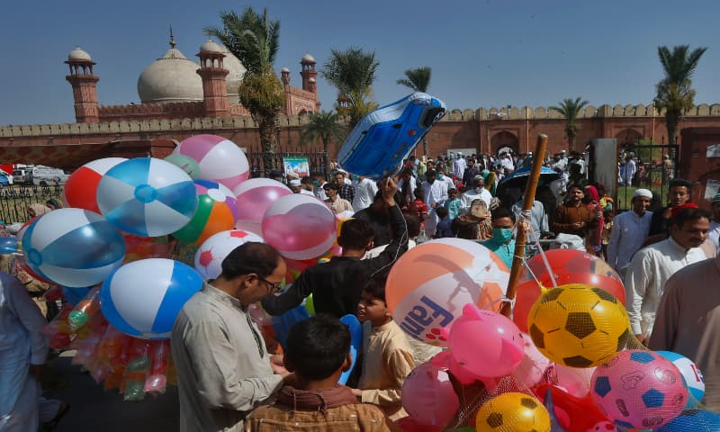 People buy balloons for their children after attending Eidul Fitr prayer at the historical Badshahi mosque in Lahore, on Sunday, May 24, 2020. — AP