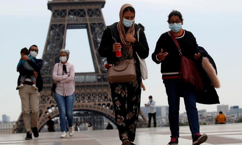 People wearing face masks walk at Trocadero square near the Eiffel Tower, as France began a gradual end to a nationwide lockdown due to the coronavirus. — Reuters/File