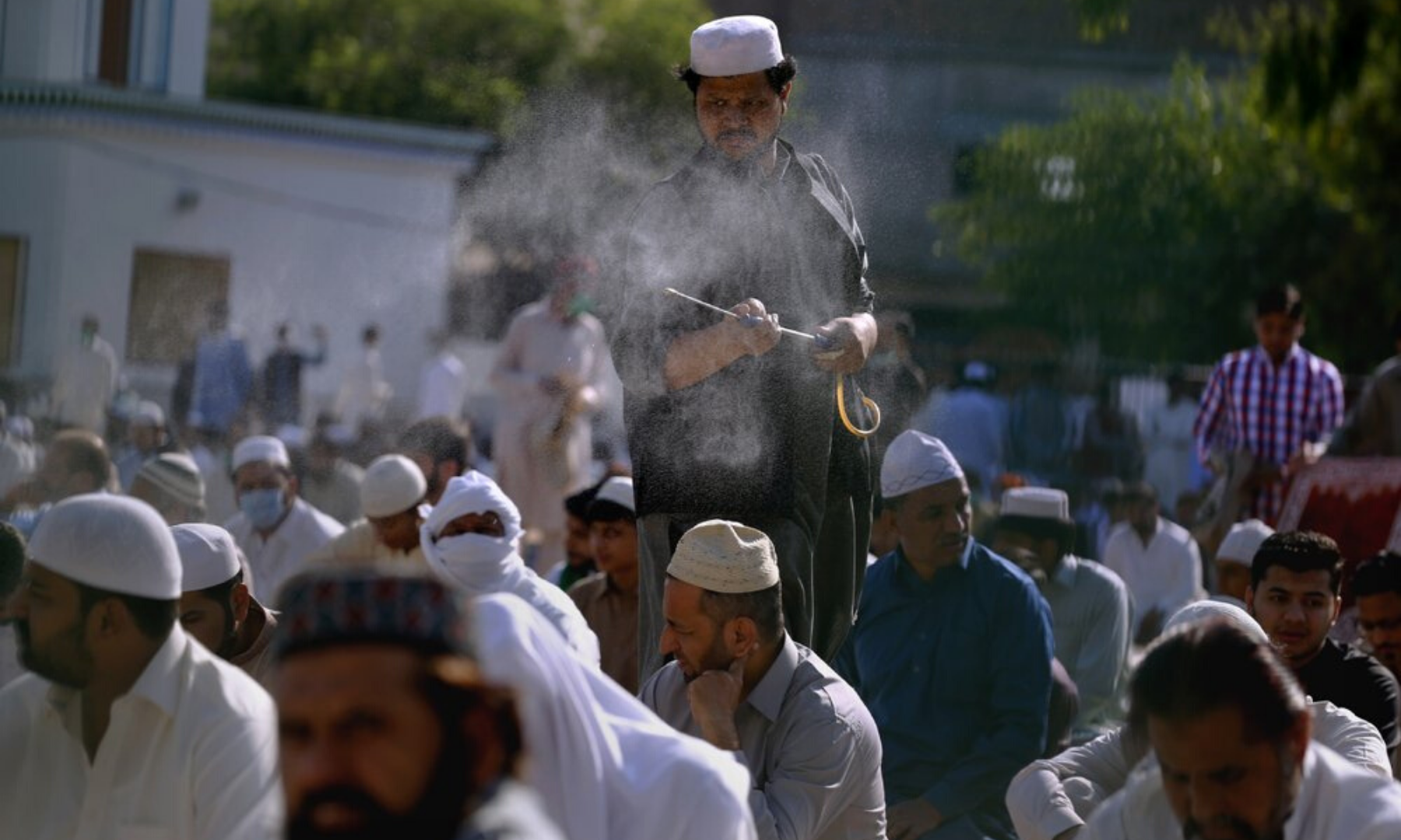 A worker sprays disinfectant among worshippers attending the Eidul Fitr prayer at a ground in Rawalpindi. The 20-point agenda agreed between the government and the ulema for congregational prayers included the disinfection of mosques. — AP