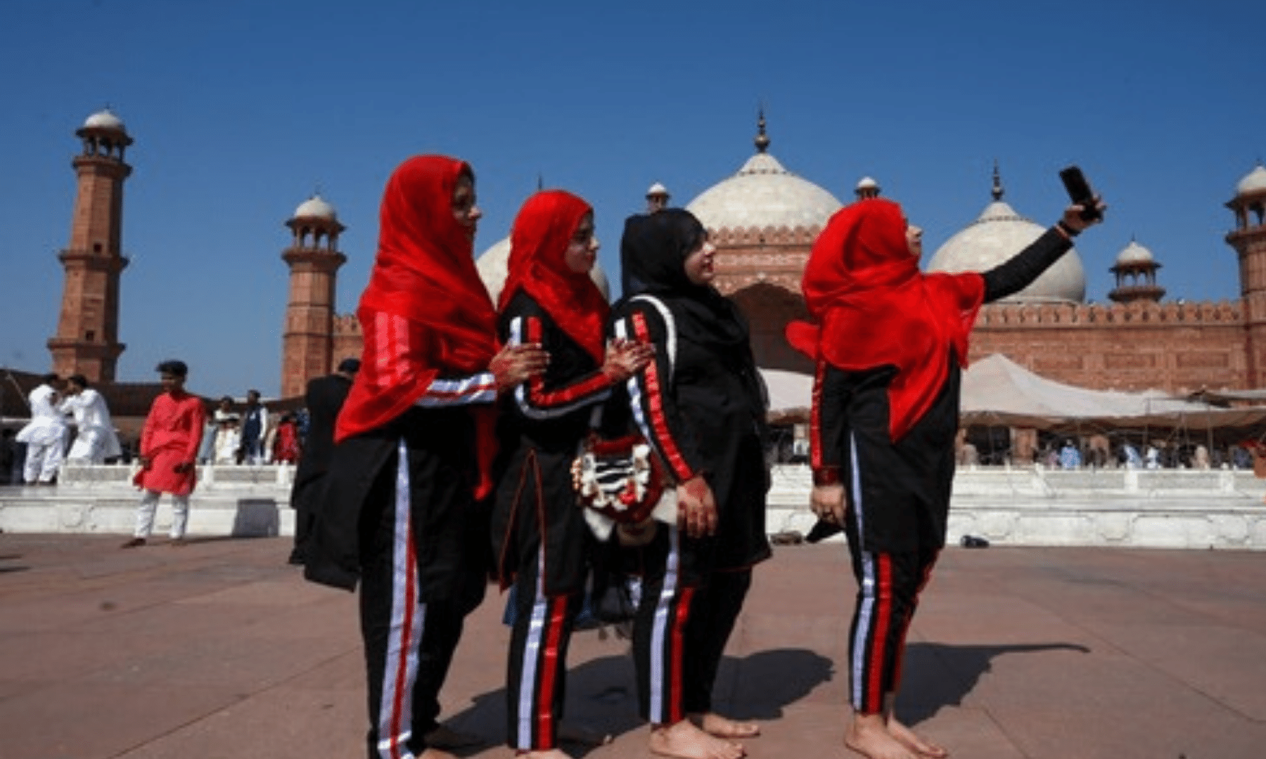 Women take selfies after offering Eidul Fitr prayers at the Badshahi Mosque in Lahore. — AFP