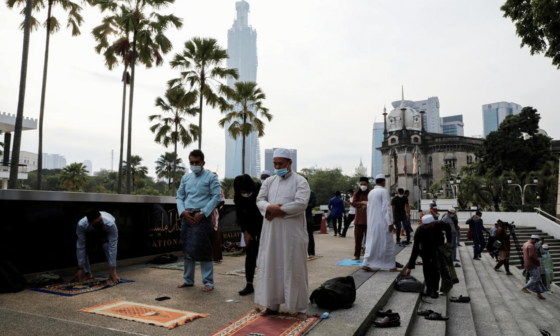 Muslims disperse after they were warned by police officers outside the closed National Mosque while celebrating Eidul Fitr in Kuala Lampur, Malaysia. —Reuters