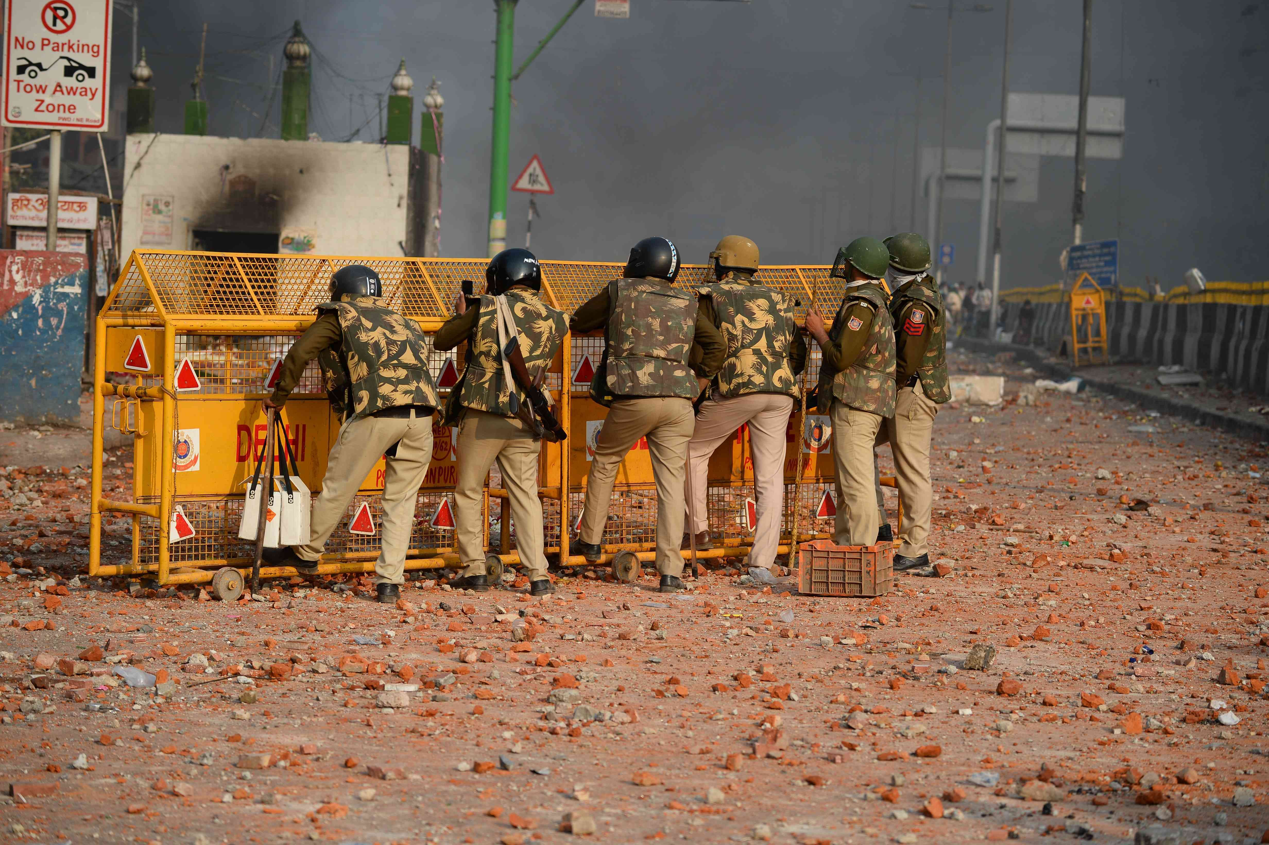 Policemen shelter behind a barrier following clashes in the Bhajanpura area of New Delhi on February 24. — AFP