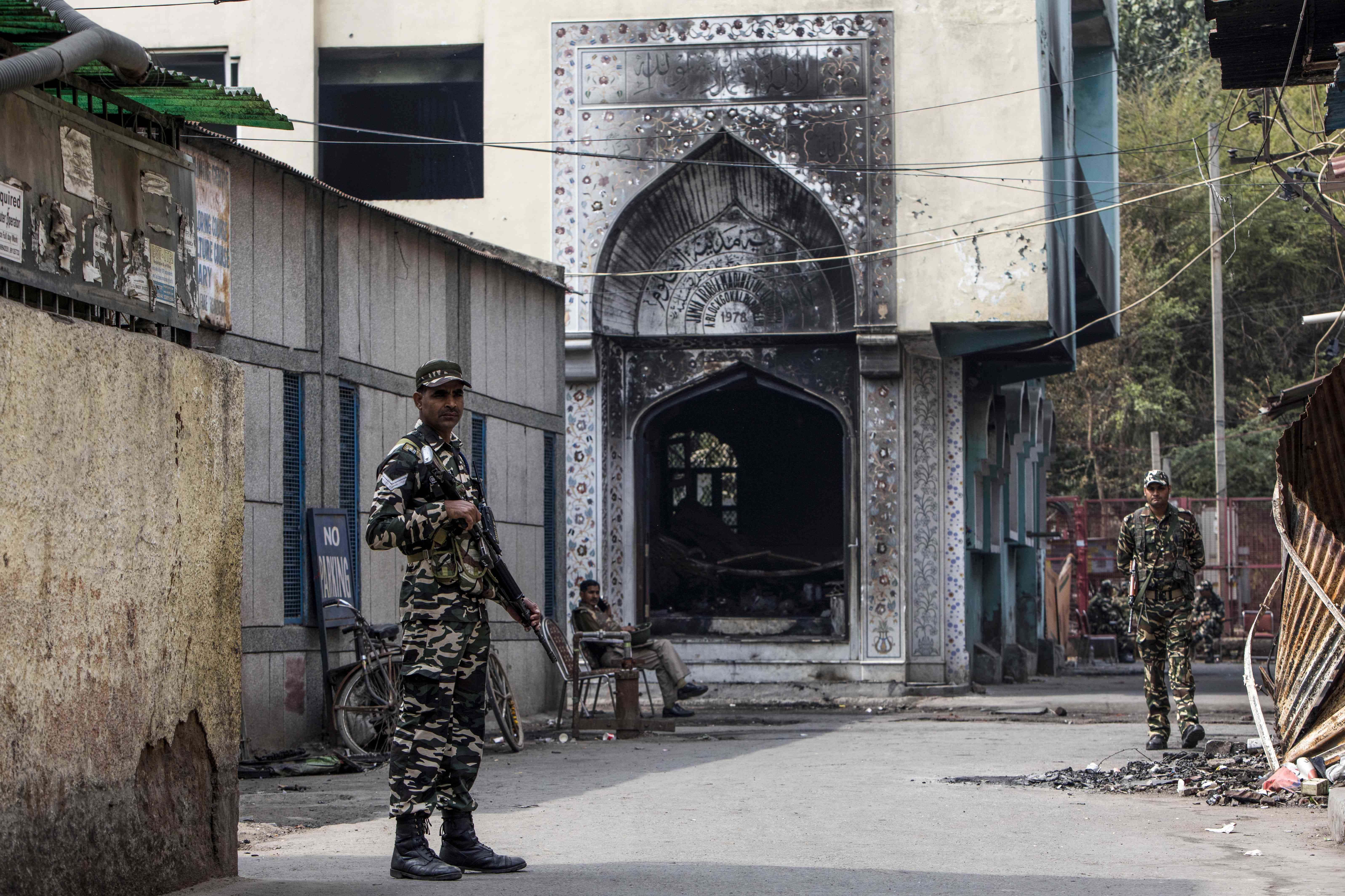 Security personnel stand guard outside a burnt-out mosque in Mustafabad in New Delhi on February 28. — AFP