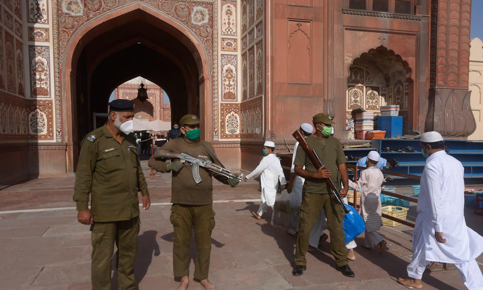 تاریخی بادشاہی مسجد کے بعد باہر عیدالفطر کی نماز سے قبل پولیس اہلکار چوکس کھڑے ہیں — فوٹو: اے پی