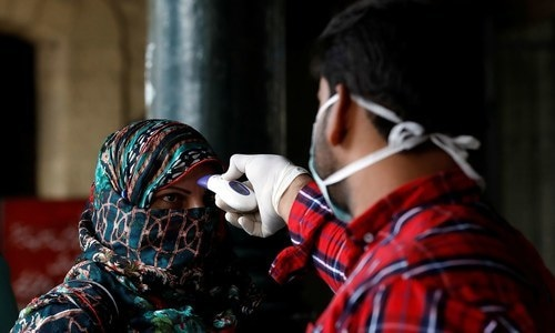 A health worker checks a woman's temperature amid coronavirus fears, at a counter at the Cantonment railway station in Karachi. — Reuters