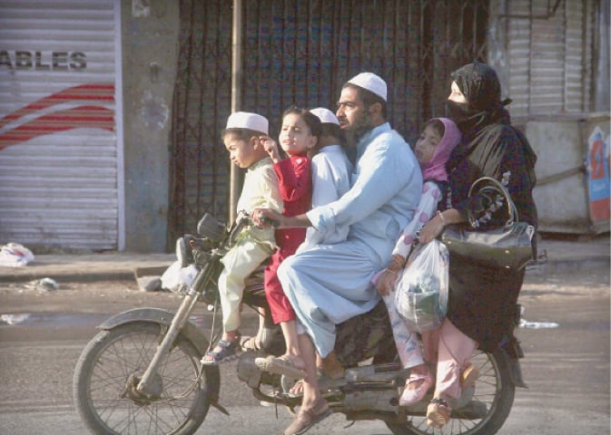 A MAN rides the overloaded motorbike as part of Eid celebrations, risking his and family's lives.—Online