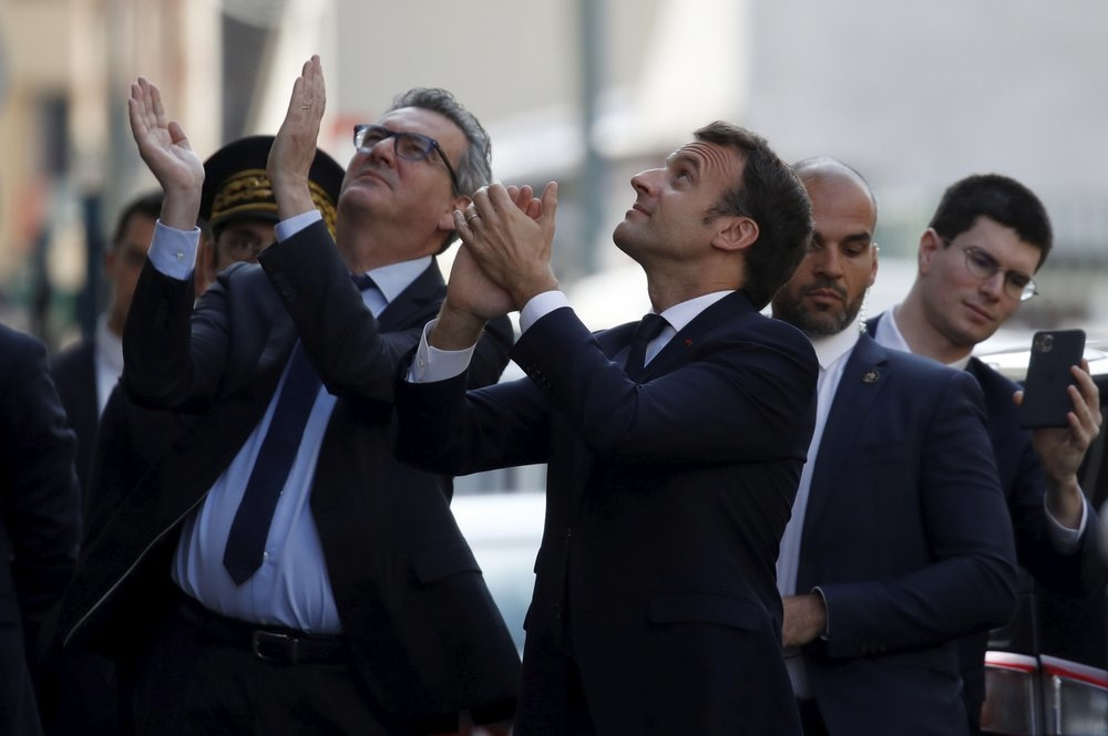 In this April 7 file photo, French President Emmanuel Macron, centre, wearing no face mask, applauds residents with officials and body guard just beside him, after visiting a medical centre in Pantin, near Paris. — AP