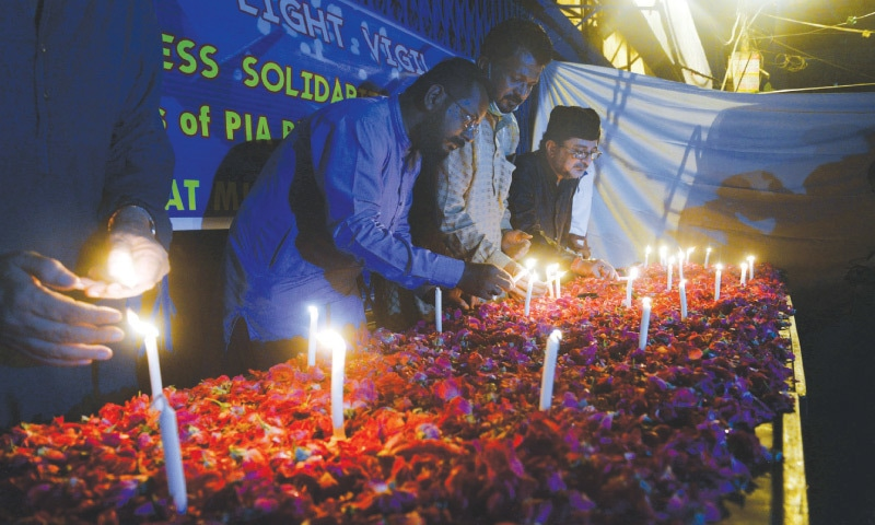 Activists of the Majlis-i-Wahdatul Muslimeen light candles in memory of the plane crash victims at Numaish Chowrangi on Wednesday evening.—Shakil Adil / White Star
