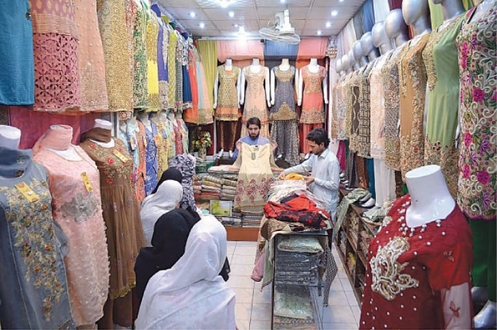 PESHAWAR: Vendors display clothes to customers at Saddar Bazaar. The ILO says that the pandemic continues to cause an unprecedented reduction in economic activity, with an estimated 4.8 per cent of working hours lost during the first quarter of 2020.—APP