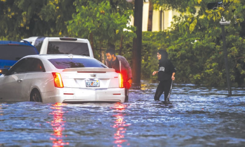 MIAMI: People walk in flooded water during heavy rainfall on Tuesday.—AFP