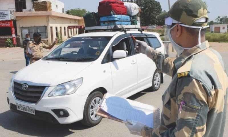 بھارتی بارڈر سیکیورٹی فورس کا اہلکار وطن واپس آنے والے پاکستانی شہریوں کے نام فہرست میں تلاش کرتے ہوئے—تصویر: اے ایف پی