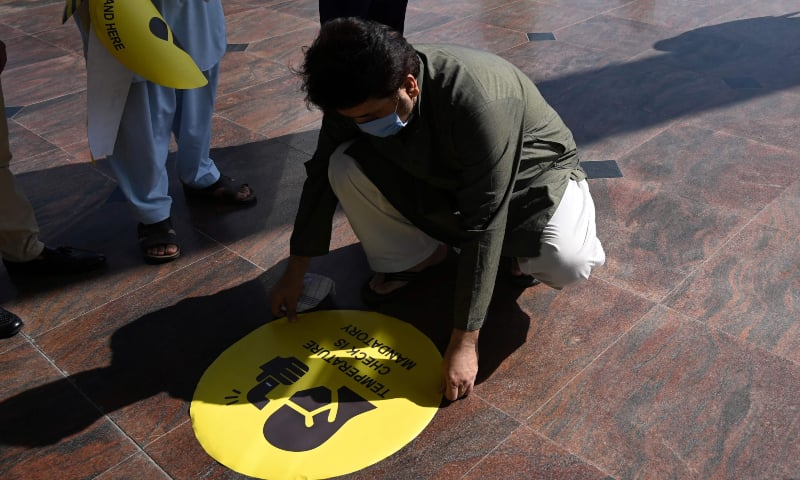 In this picture taken on May 18, 2020, a shopping mall official tags a scan sign on the floor at the main entrance of the Centaurus Mall. — AFP