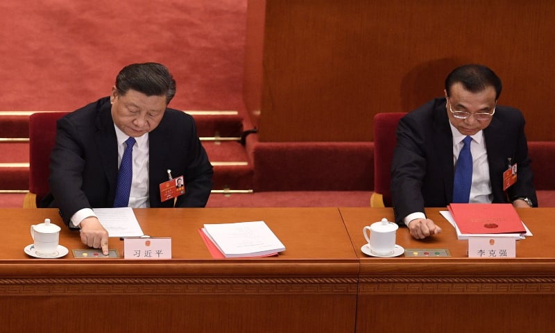 Chinese President Xi Jinping (L) and Premier Li Keqiang vote on a proposal to draft a security law on Hong Kong during the closing session of the National People's Congress at the Great Hall of the People in Beijing on May 28, 2020. — AFP