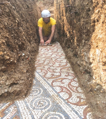 This photo released on Thursday shows an archaeologist uncovering an ancient Roman mosaic floor discovered under vines in the Italian region of Negrar, near Verona.—AFP