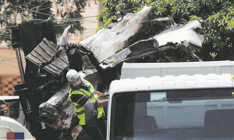 Karachi: A worker reacts as a truck is loaded with the wreckage of the crashed PIA plane on Thursday.—Reuters