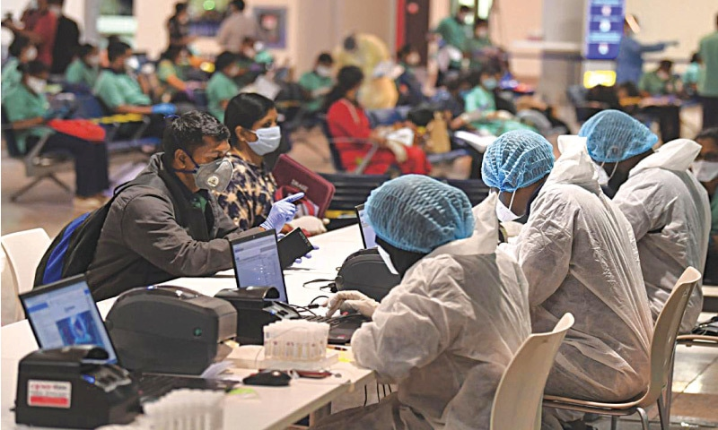 Members of an Indian medical team register for testing upon their arrival at Dubai International Airport to help with the coronavirus pandemic | Photo: AFP