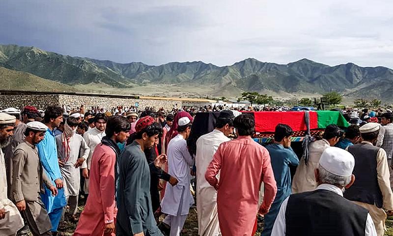افغان شہری طالبان کے حملے میں ہلاک سیکیورٹی فورسز کے اہلکار کے جسد خاکی کو تدفین کے لیے لے جا رہے ہیں— فوٹو: اے ایف پی
