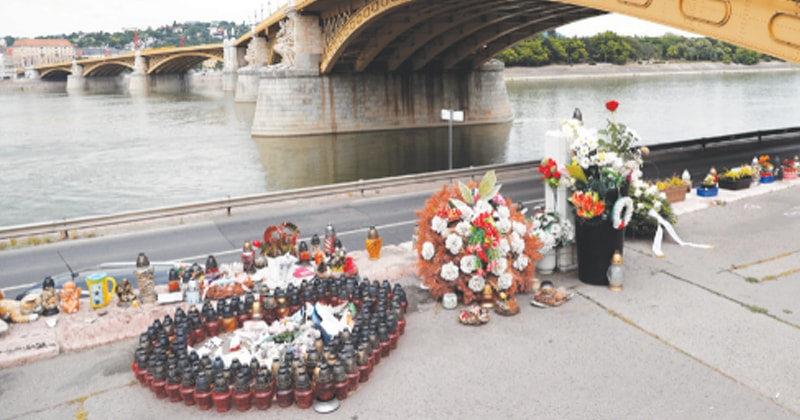 BUDAPEST (Hungary): Flowers and candles are placed near a bridge to honour the victims of the Mermaid boat accident on the first anniversary of the tragedy on Friday.—Reuters
