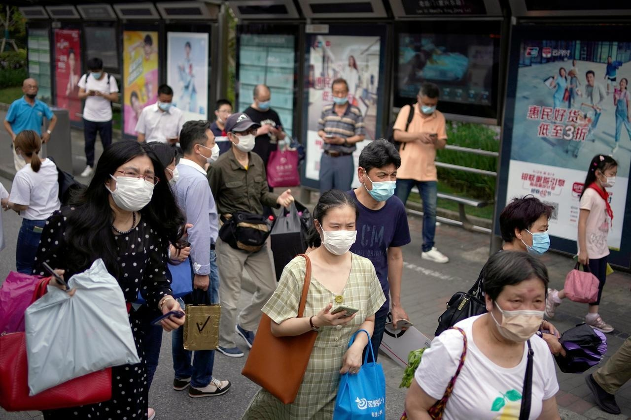 People wearing protective face masks are seen on a street following an outbreak of the novel coronavirus  in Shanghai, China on May 28. — Reuters