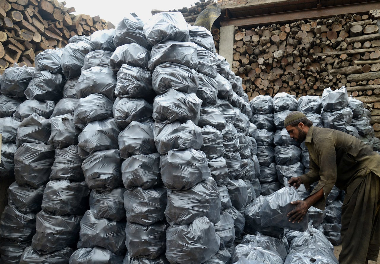 A man stacks bags of coal in Peshawar | Abdul Majid Goraya/White Star
