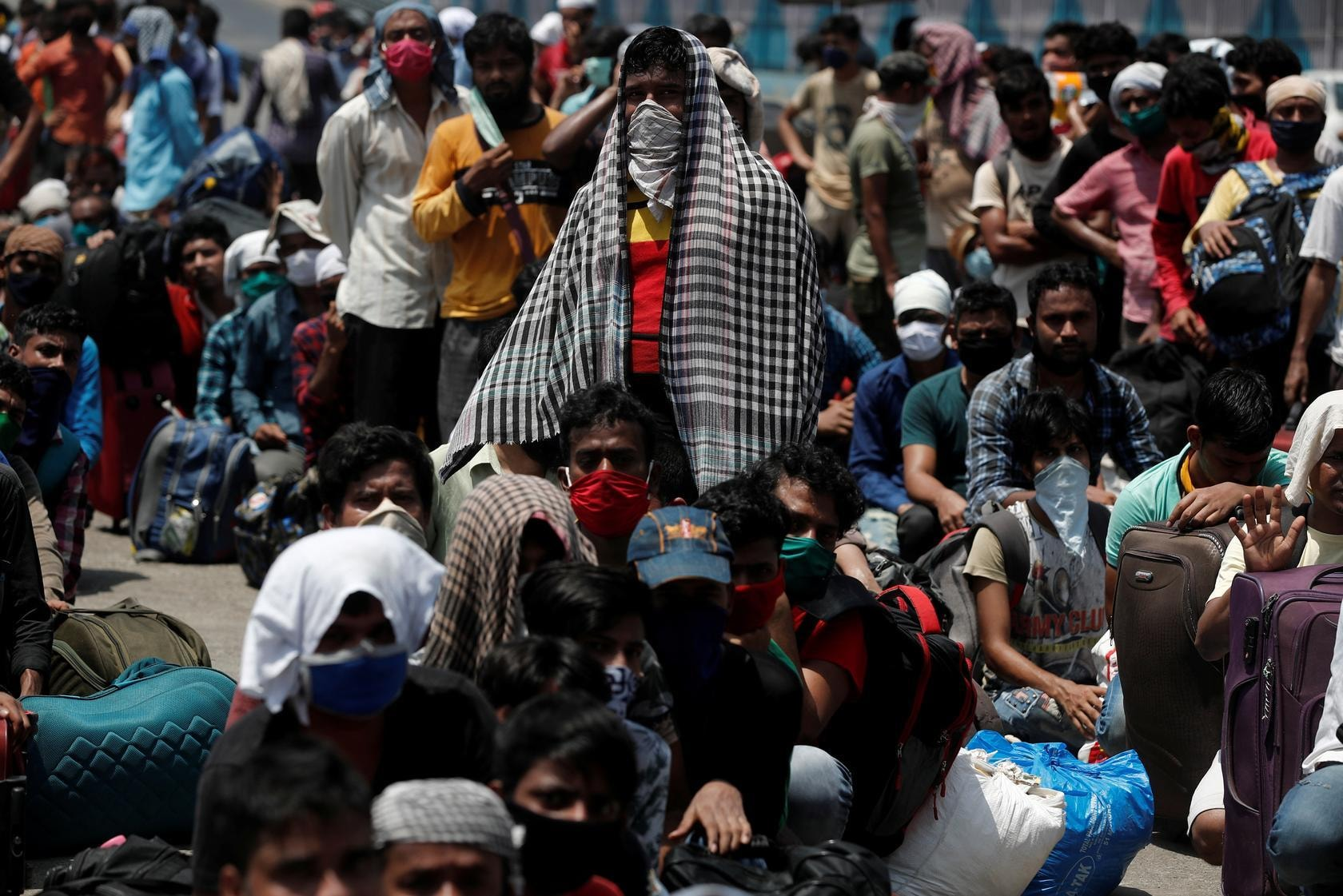 People wait in a line to board a train that will take them to their home state of Uttar Pradesh, during an extended lockdown to slow the spreading of the coronavirus disease, in Mumbai, India, May 26. — Reuters