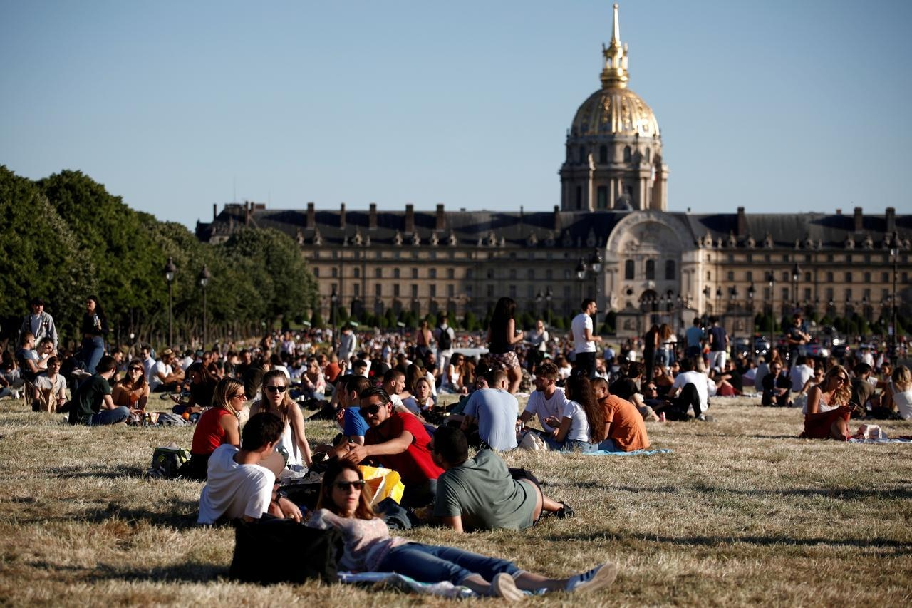 People enjoy the hot weather next to the Invalides Museum in Paris, as France gradually lifts its Covid-19 lockdown, on May 29. — Reuters