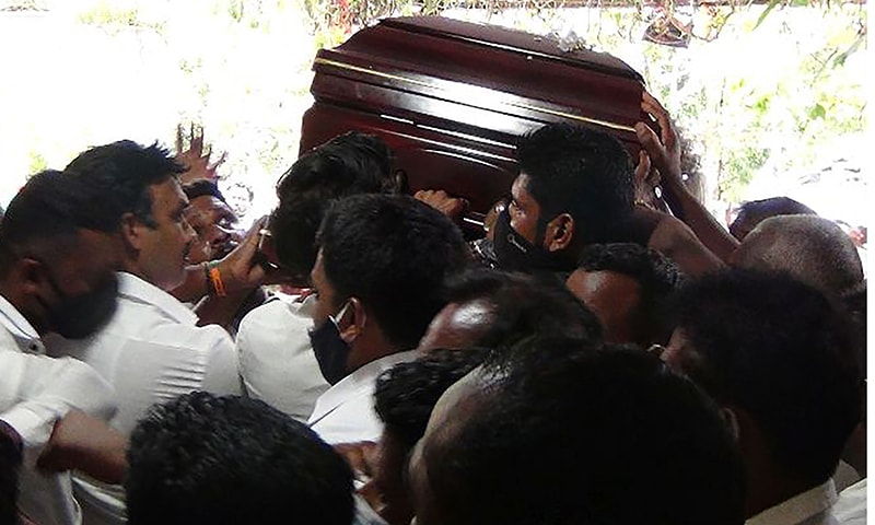 Party supporters breaching social distancing rules carry the coffin of Arumugam Thondaman at his home constituency in Nuwara Eliya district on May 30. — AFP