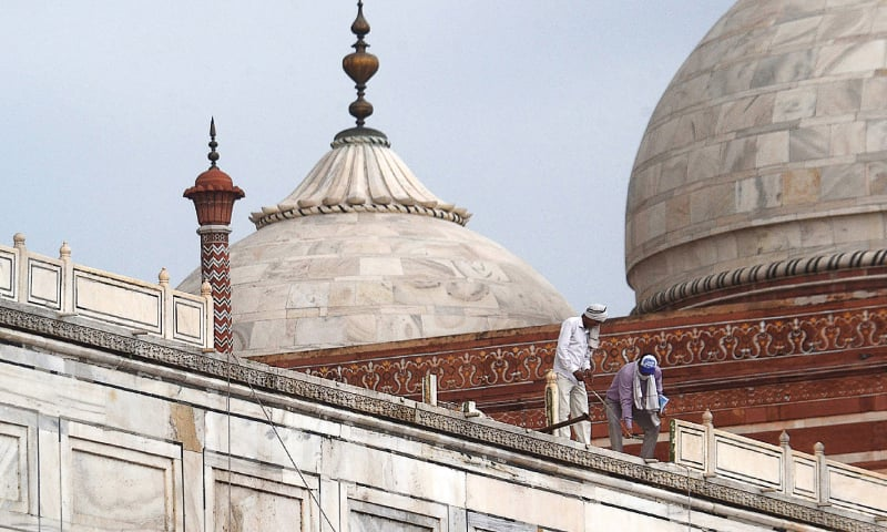 AGRA: Workers examining a damaged railing at the Unesco World Heritage Site.—AFP