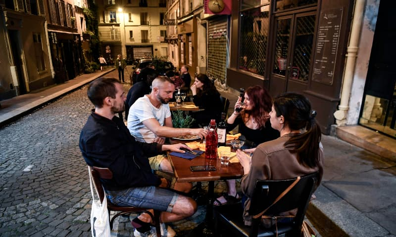 People sit and drink at a restaurant terrace in Montmartre on May 31, 2020 in Paris, as France eases lockdown measures taken to curb the spread of the Covid-19 pandemic. — AFP