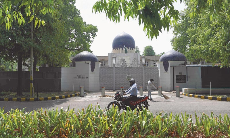 NEW DELHI: A motorcyclist rides past the main gate of the Pakistan High Commission on Monday.—AFP