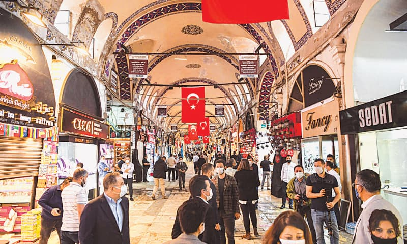 Istanbul: People wearing protective face masks walk through Istanbul's  Grand Bazaar after the reopening of restaurants and cafes on Monday.—AFP