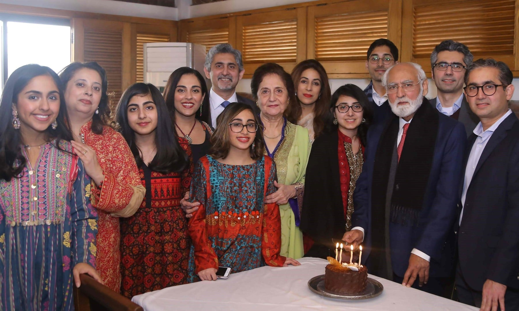 This handout picture taken on March 26 and received as a courtesy of the Adil Rahman family shows Fazal Rahmaan (3R) celebrating his 80th birthday with his wife Wahida Fazal Rahmaan (C-green dress) and family members in Lahore. — AFP