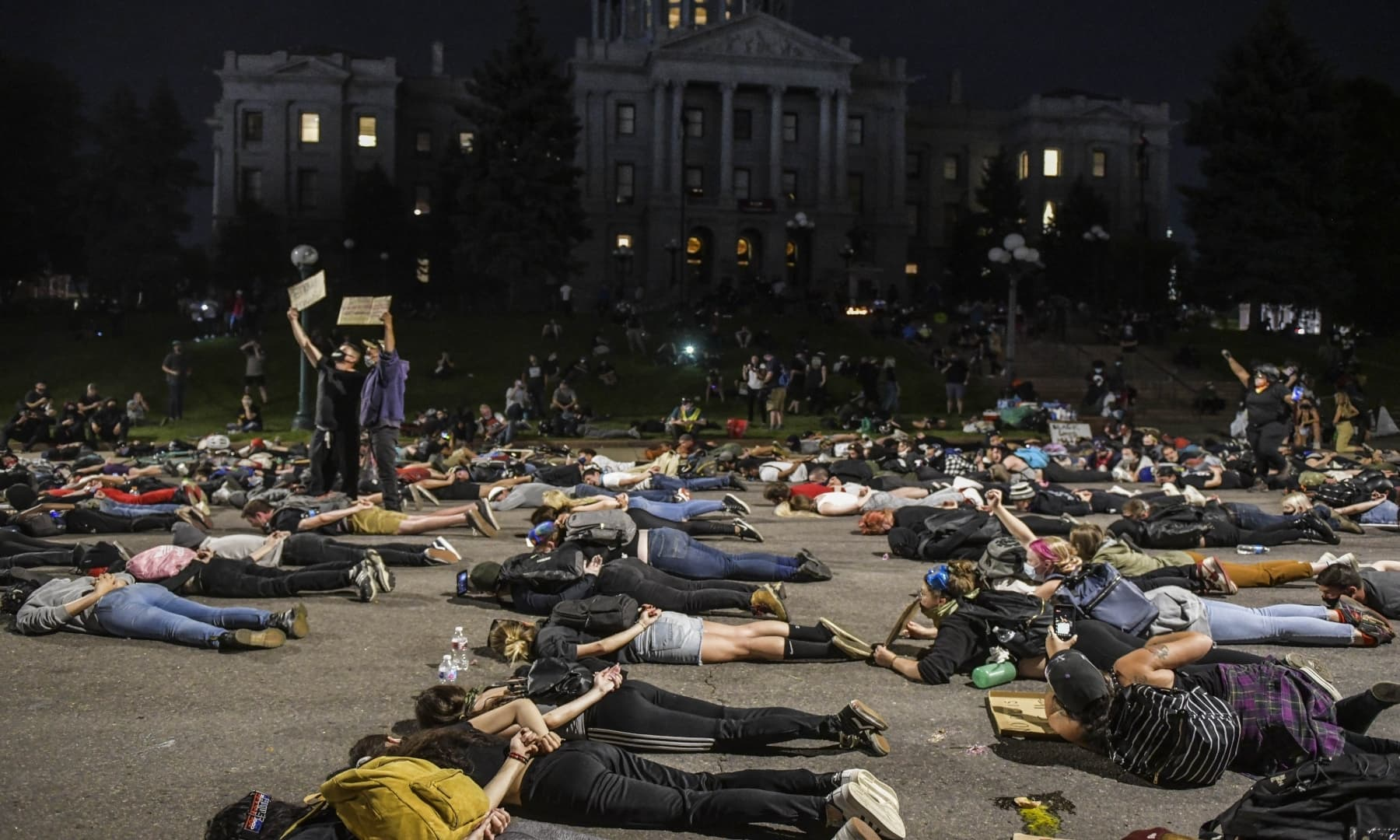 People lie down in the middle of the street in front of the Colorado State Capitol to protest on June 1, in Denver, Colorado. — AFP