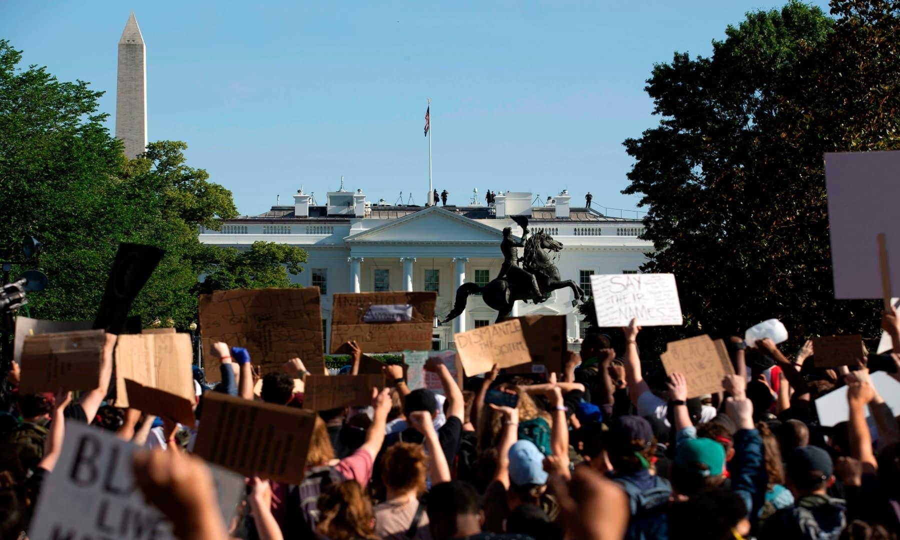 Demonstrators hold up placards protest outside of the White House, over the death of George Floyd, in Washington DC on June 1. — AFP
