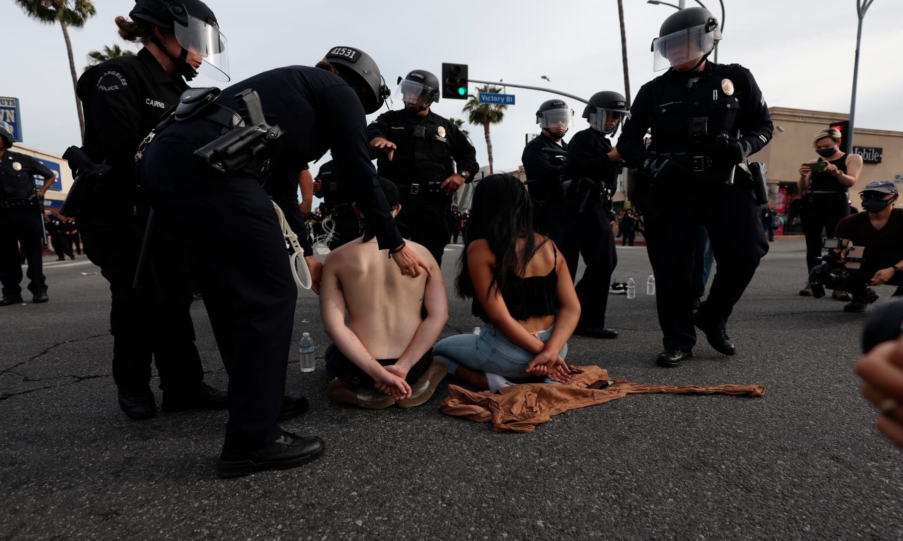 Television personality, Kai Wes, left, and college student, Wendy Chavez, right, are arrested for violating a county-wide curfew at a protest in Van Nuys,  on June 1, 2020. — AP