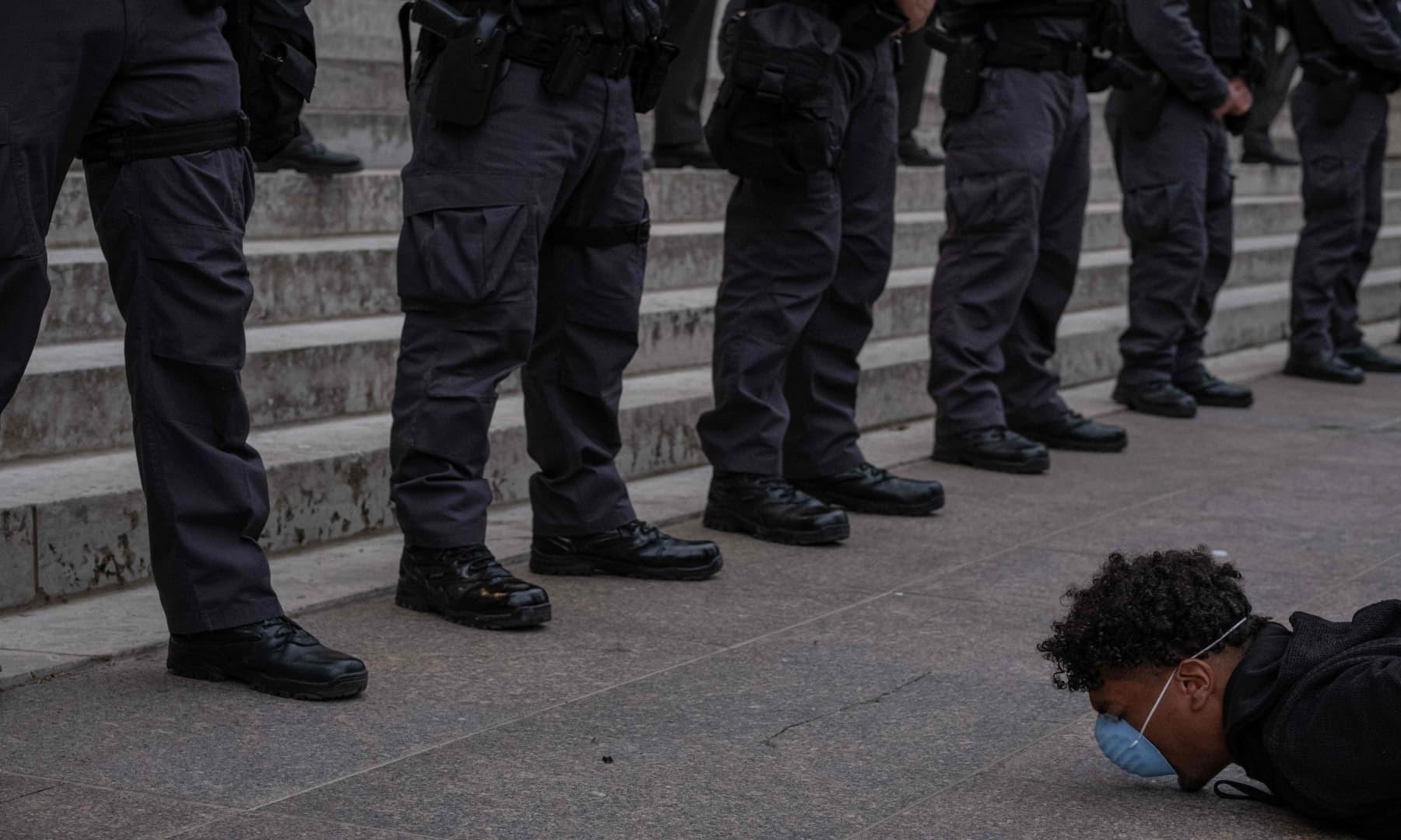 نیویارک میں ایک شخص احتجاج کے دوران سیکیورٹی اہلکاروں کے سامنے لیٹا ہوا ہے — فوٹو: اے ایف پی