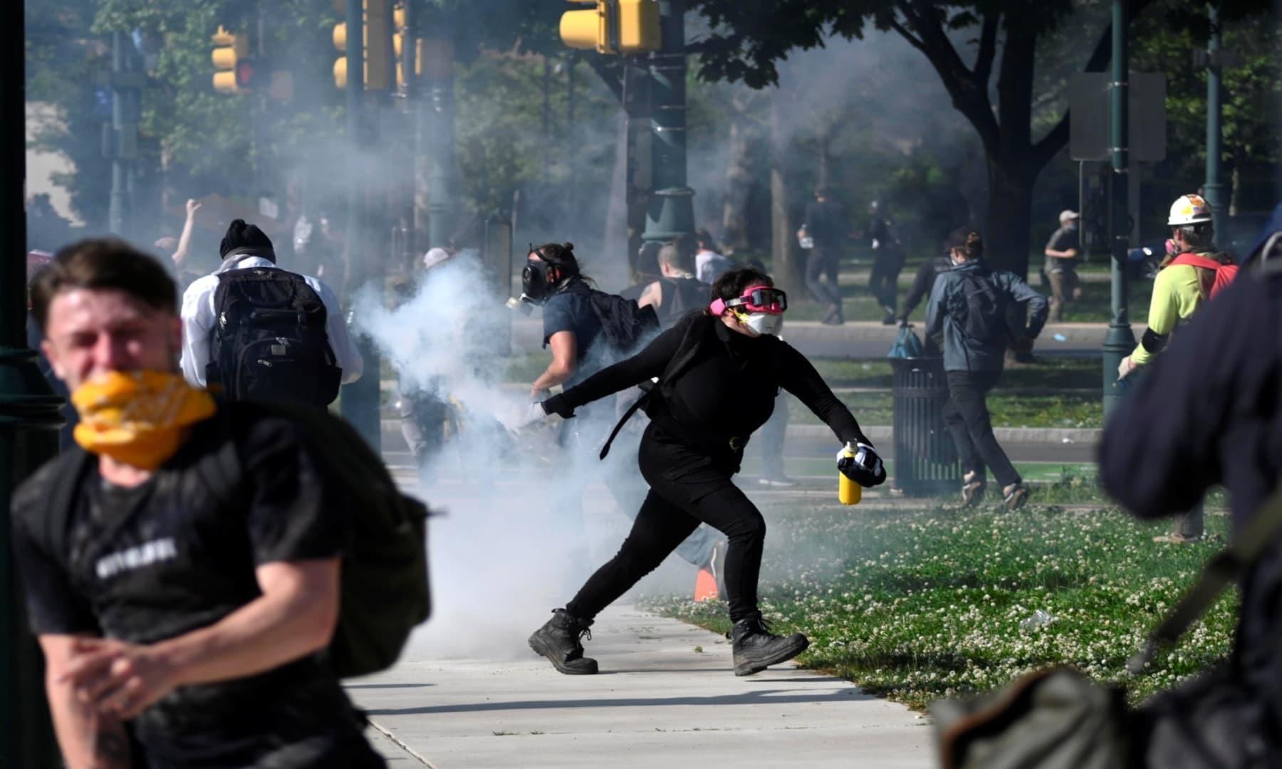 پینسلویلیا میں مظاہرین پولیس کی جانب سے کی جانے والی آنسو گیس کی شیلنگ میں شیل واپس اہلکاروں کی جانب پھینک رہے ہیں— فوٹو: رائٹرز