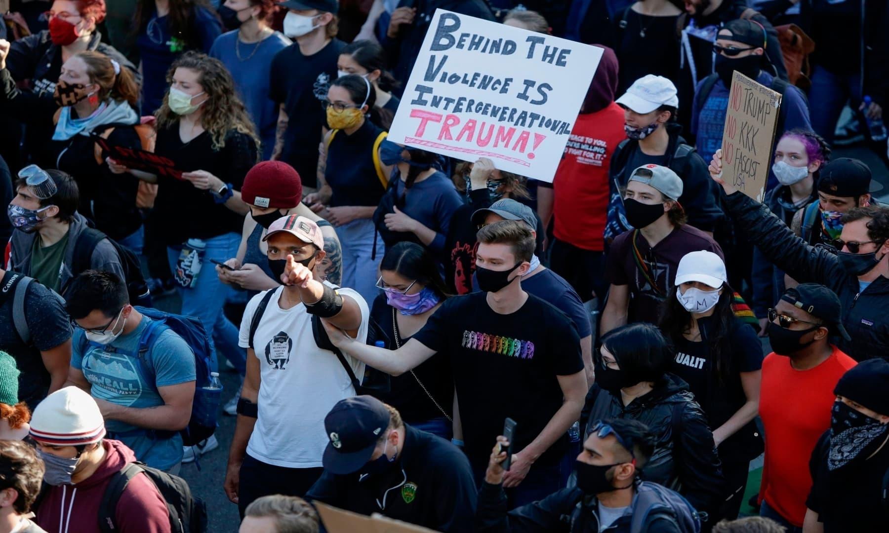 مظاہرین نے احتجاج کے دوران پلے کارڈ اٹھا رکھیں ہیں  — فوٹو: اے ایف پی