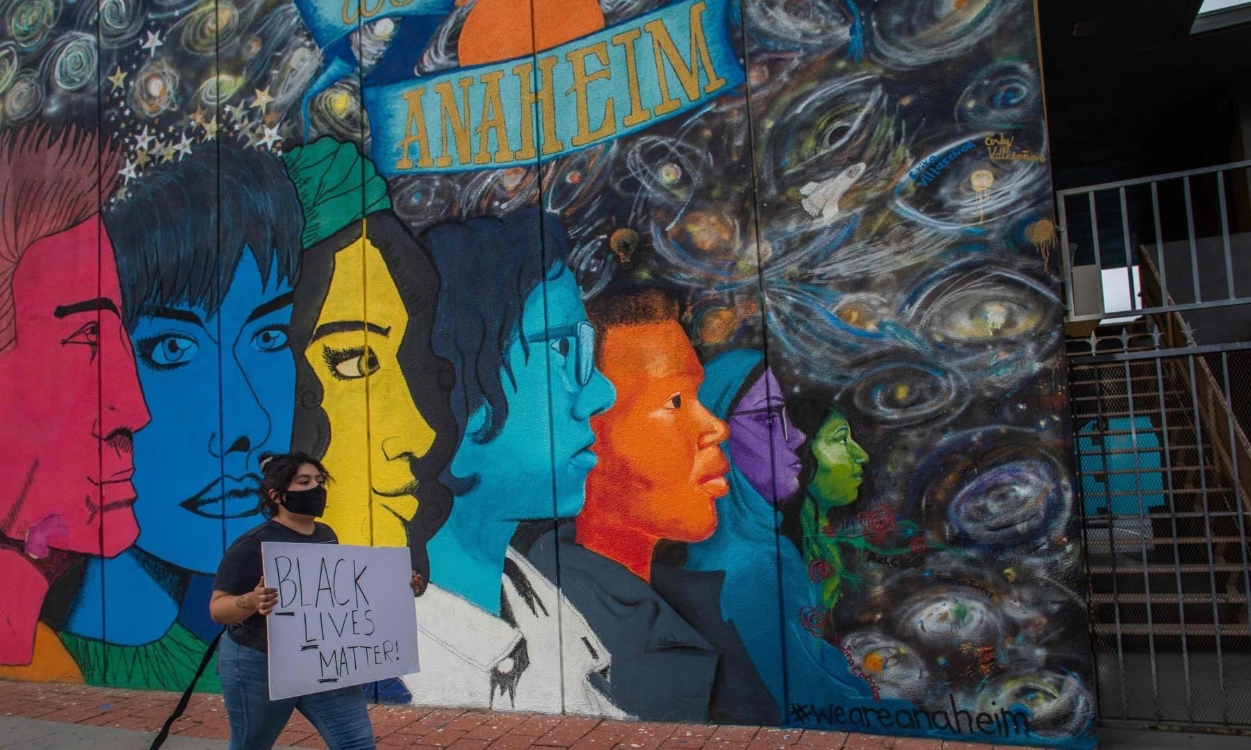 کیلیفورنیا میں مظاہرے کے دوران مارچ میں شریک خاتون نے پلے کارڈ اٹھایا ہوا ہے— فوٹو: اے ایف پی