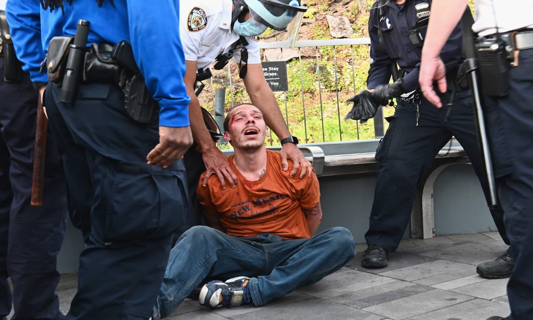 سیاہ فارم برادری کے حق میں کیے جانے والے مظاہروں میں زخمی ہونے والے ایک شخص کو پولیس گرفتار کر رہی ہے— فوٹو: اے ایف پی