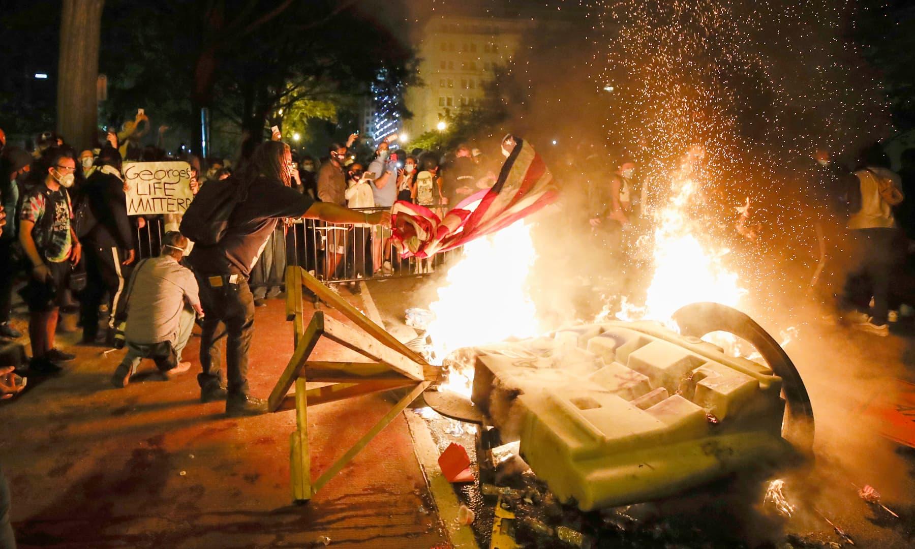 وائٹ ہاؤس کے باہر جلاؤ گھیراؤ کا ایک منظر— فوٹو: اے ایف پی