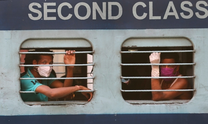 In this May 23 photo, Indian migrant workers look out from the window of a train in Hyderabad, India as they return to villages. — AP