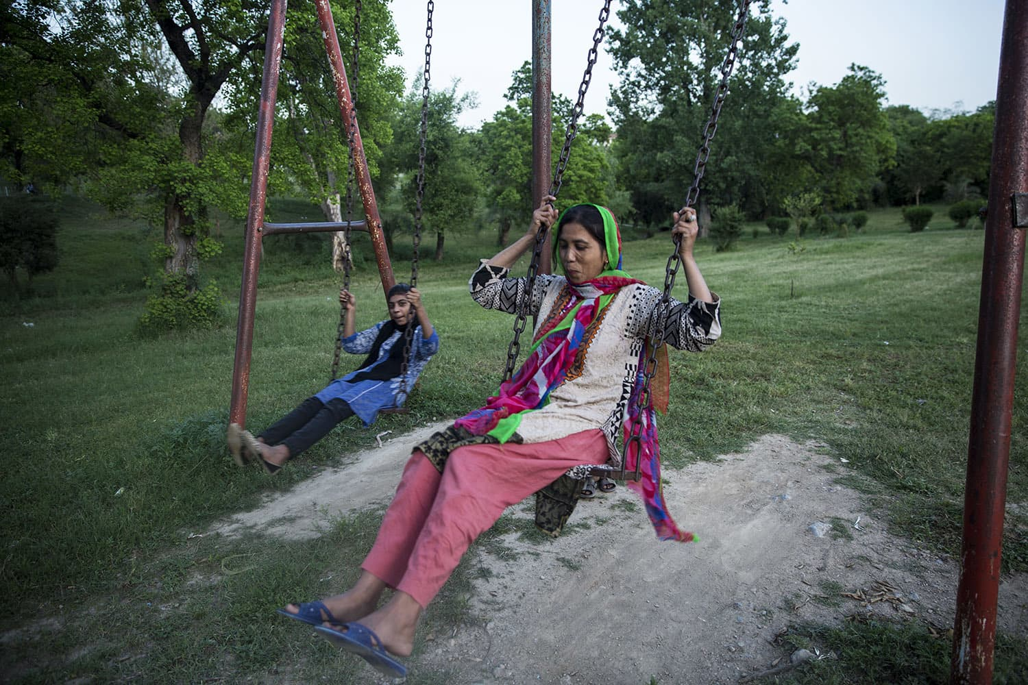 Ishrat sits on a swing during the family's visit to the park. Going to the park not only serves as a respite for the children but also for adults, April 30, 2020 in Islamabad.