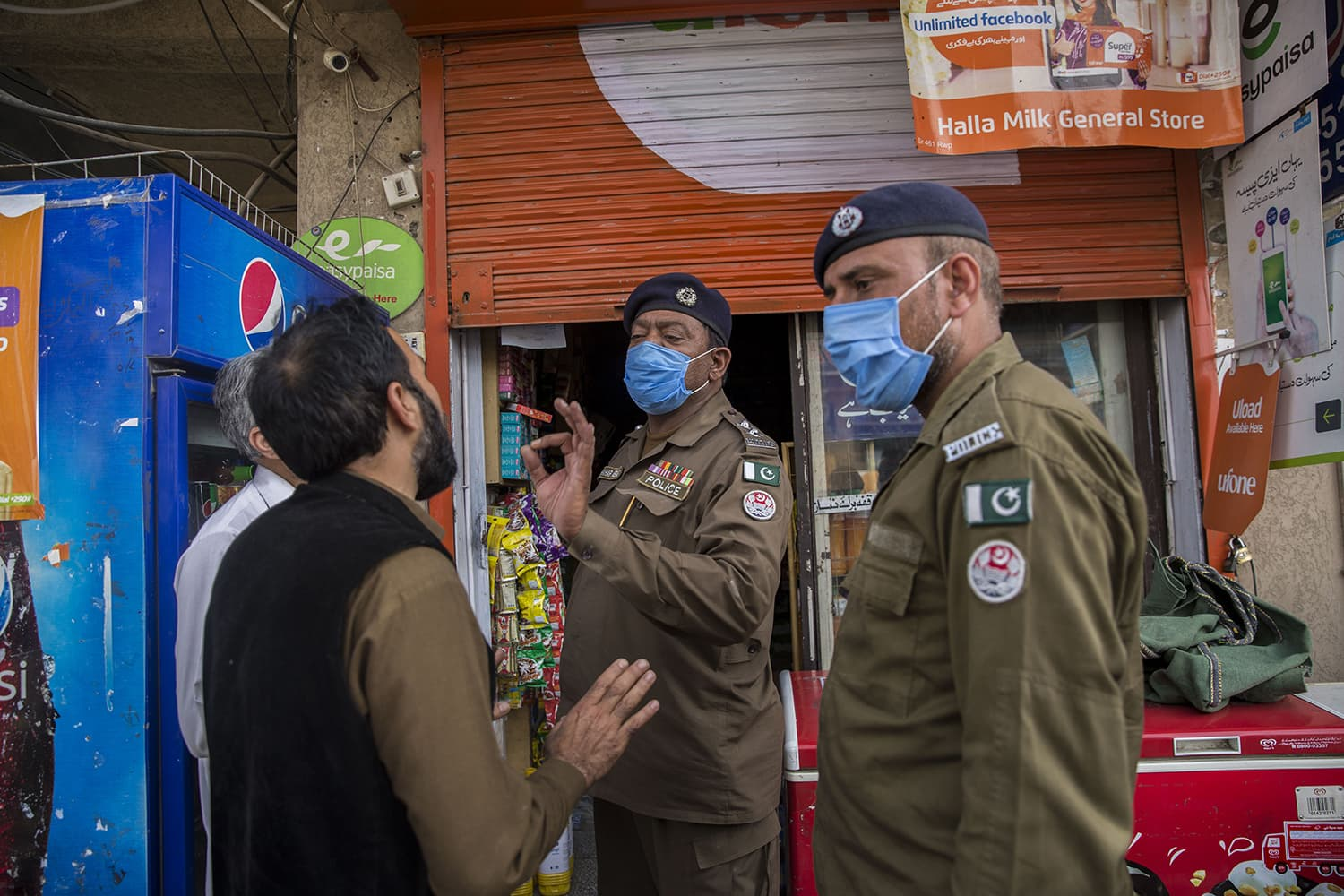 Sub-Inspector Fakhar Abbas telling shopkeepers to close down and abide by the 5pm call to shutdown shops, May 6, 2020, in Rawalpindi.